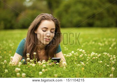 Young beautiful woman lying on the grass reading a message on a cell phone