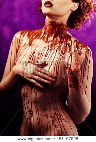 Beautiful sexy young woman. Body covered with a blood. Studio shot