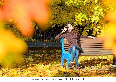 Attractive young woman sitting on brown wooden bench with her hands behind her head in beautiful park. She close her eyes. Golden autumn foliage around. Girl wears blue jeans and turtleneck sweater. Yellow color dominates