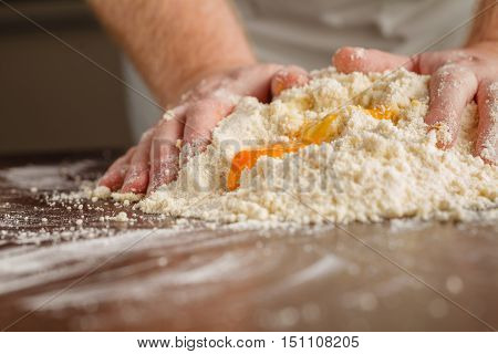 Handful Of Flour With Egg On A Rustic Kitchen. Against The Background Of Men's Hands Knead The Dough