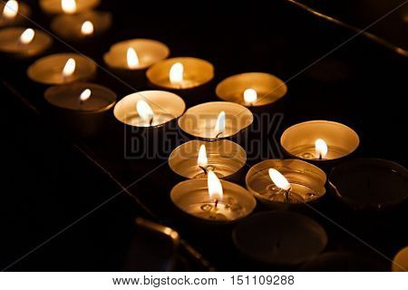 Rows of burning candles in a dim church