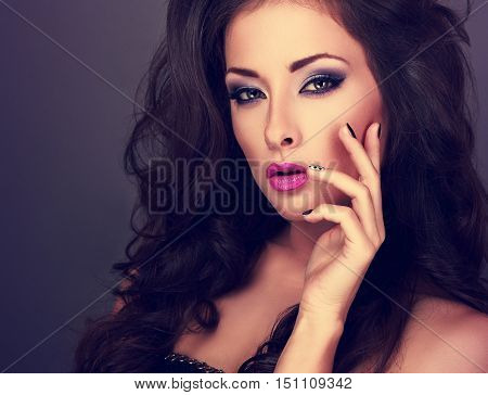 Beautiful Fashionable Bright Makeup Woman With Long Curly Volume Hair And Manicured Fingers On Blue