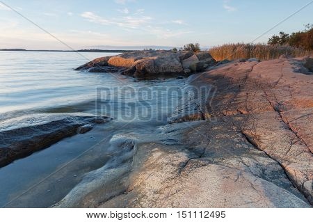 Cliffs blue sea warm light and horizon during sunset in the archipelago