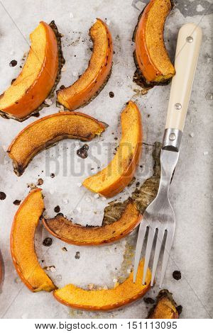 roasted hokkaido pumpkin wedges with salt and black pepper on kitchen paper with a fork