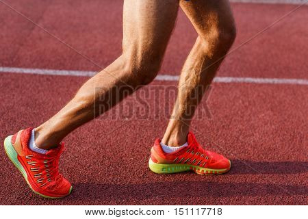 Close-up image of male legs and feet on cross track outdoors
