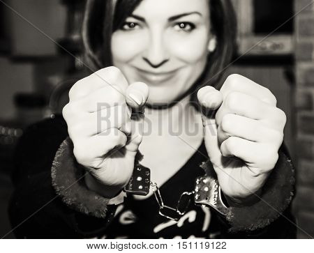 Young caucasian woman posing with handcuffs at the party. Sexy female portrait. Crime theme. Submissive role. Black and white photo.