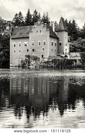 Cervena Lhota is a beautiful chateau in Czech republic. It stands at the middle of a lake on a rocky island. Travel destination. Beautiful place. Black and white photo. Mirrored architecture.