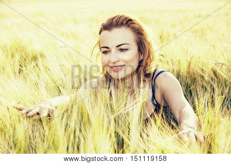 Sexy caucasian woman in the wheat cobs by sunset. Natural beauty. Backlight scene. Retro photo filter. Female portrait. Positive emotions.