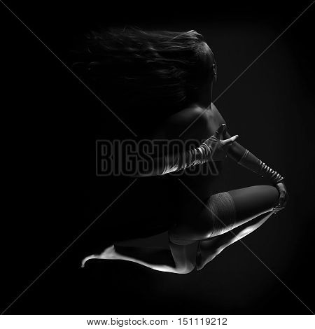 Low key greyscale photo of long beautiful sexy female floating in moonlight with montion trails in white stockings and belt hands in gloves against dark background