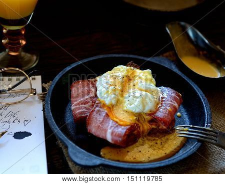 toast with bacon and poached egg in a frying pan