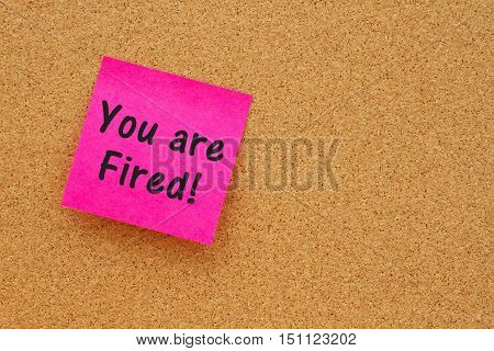 You are fired message Bulletin board with a pink sticky note with text you are fired