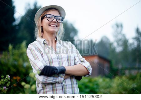 Portrait of happy smiling young woman gardener with gloves standing in the middle of her possessions