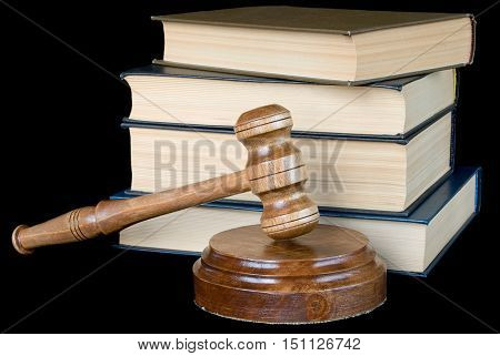 Wood gavel soundblock and stack of thick old books isolated on a black background