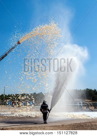 firefighter holding a fire hose with water pressure a demonstration of fire fighting equipment.