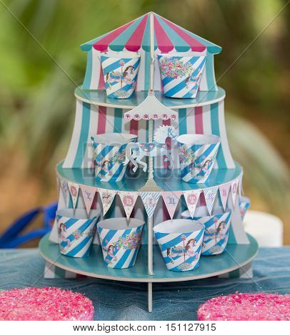 Colorful striped blue and pink birthday carousel with matching striped paper cups standing on a table at an outdoor buffet celebration