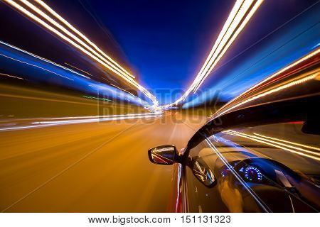 poster of The car moves at great speed at the night. Blured road with lights with car on high speed.