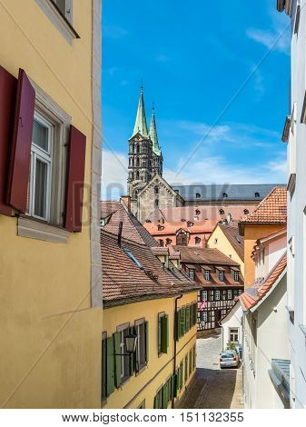 Bamberg Germany - May 22 2016: View of a typical old narrow street in the historical center of UNESCO world heritage town Bamberg Bavaria Germany. Bamberg Cathedral in the background.