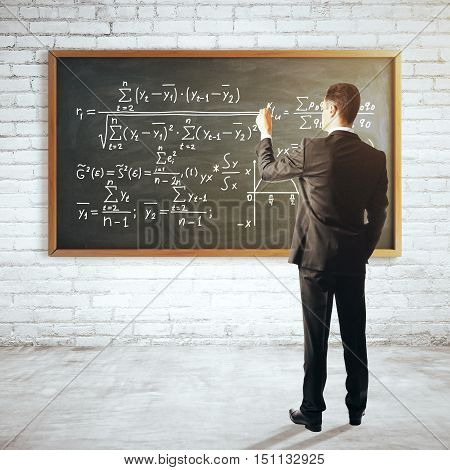 Back view of young businessman in suit writing mathematical formulas on chalkboard hanging in white brick interior. Education concept. 3D Rendering