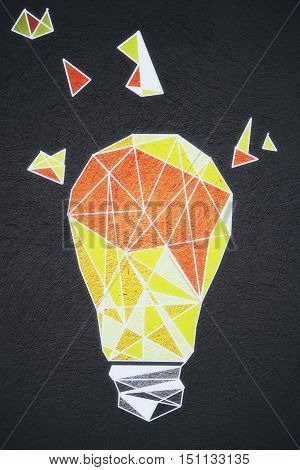 Abstract yellow polygonal light bulb sketch on dark background. Idea concept
