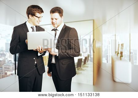 Two handsome young businessmen using laptop together in modern office