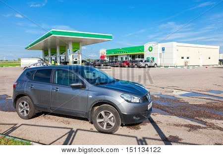 NOVGOROD REGION RUSSIA - JULY 31 2016: Car Nissan Qashqai on the background of BP petrol station. British Petroleum is a British multinational oil and gas company