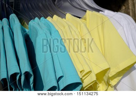 Numerous t-shirts in multiple colors on clothes hangers to choose from