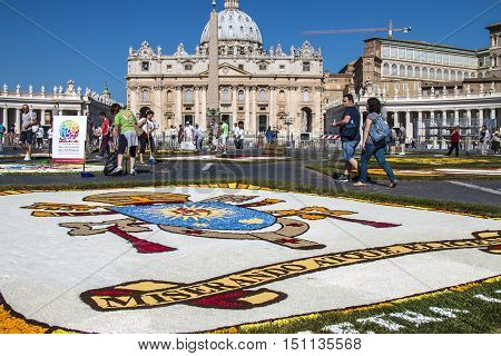 Rome Italy - June 29 2014: On the occasion of the patron saints of the city of Rome St. Paul and St. Peter was held in Piazza Pio XII and in the Via della Conciliazione Traditional Flower Festival. Some tourists admire the floral decoration with the escut