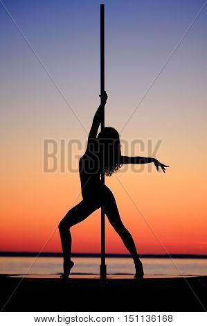 Silhouette of a girl on the pylon on sunset background