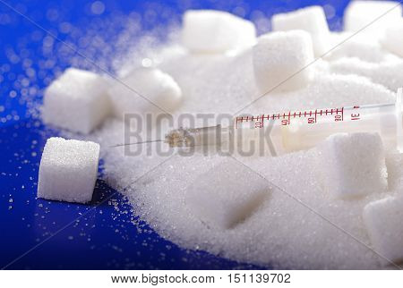 Insulin injection white a pile of sugar