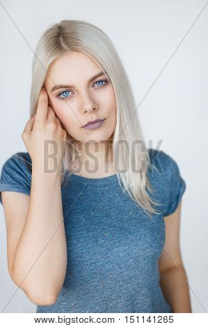 Vertical portrait of young beautiful woman with white hair posing over grey background. Clean t-shirt mockup