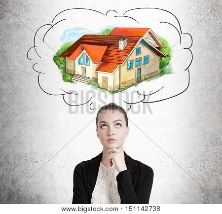 Front view of young lady dreaming about her own house in suburbs which is depicted on concrete wall. Concept of real estate and purchasing a house.
