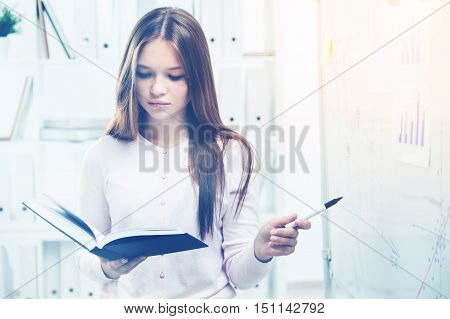 Woman Reading Black Book In Office