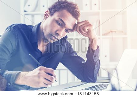 Handsome black businessman working on project on office desk with laptop and notepad. Bookshelf with documents in the background. Toned image