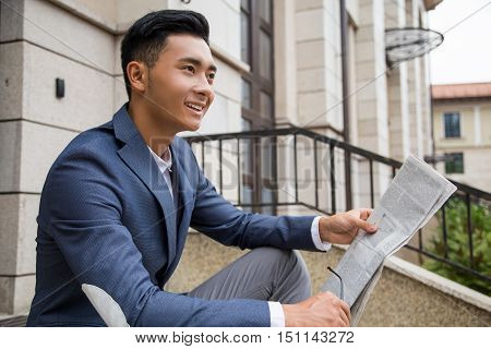 Smiling Asian businessman sitting on his front steps with fresh morning newspaper. Concept of getting your information first thing in the morning.