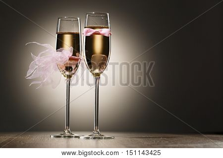 Champagne glasses decorated pink grooms bow-tie and brides veil