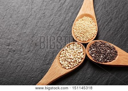Quinoa, chia and amarantus seeds in wooden spoons on a black stone background. Super foods concept. Gluten free grains. Place for text. Lovely light gradient. Top view.