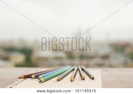 Closeup of colorful pencils on paper sheet placed on wooden windowsill. Blurry city background