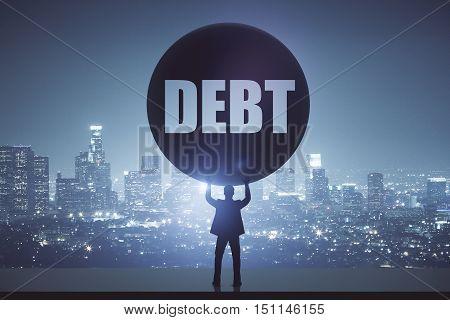 Struggling businessman holding huge ball on night city background. Debt concept