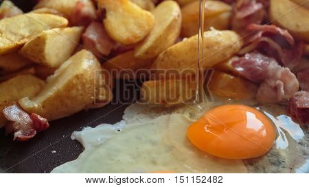 potato slices fried bacon and fried eggs in a pan