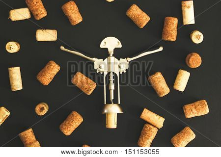 Corkscrew with many wooden corks around on the black table