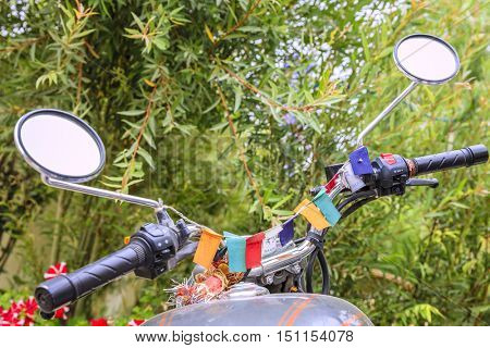 Steering bars of a motorcycle decorated with buddhist flags