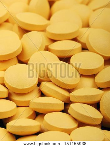 Heap of yellow medicament pills in vertical image