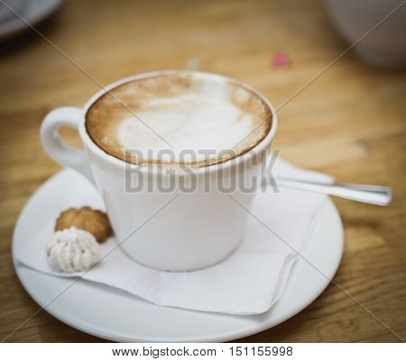 Fresh Cappuccino cup on a wooden table