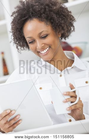 A beautiful happy mixed race African American girl or young woman using a tablet computer in her kitchen and drinking mug of coffee or tea