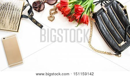 Fashion flat lay with accessories flowers phone. Feminine objects on white background