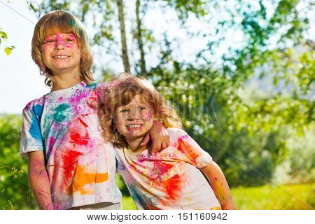 Close-up portrait of two funny age-diverse boys smeared with colored powder on Holi festival
