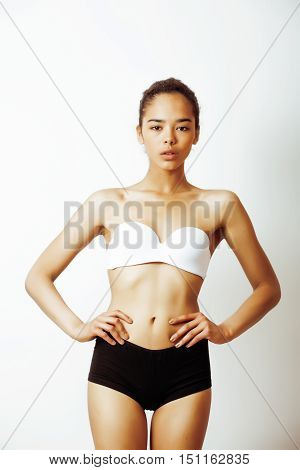 young pretty african american girl in sport underwear posing on white background, very slim loosing weight mulatto half asian multi races woman model, lifestyle people concept close up
