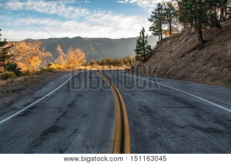 winding mountain road leading into the sunrise