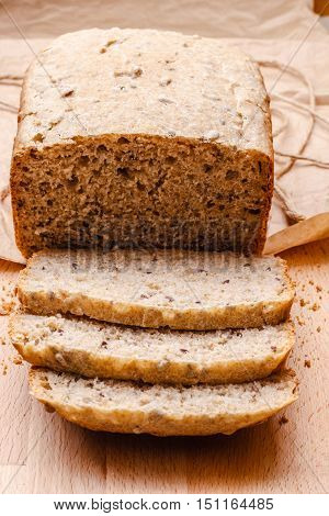 Food. Sliced whole wheat bread on cutting board wooden background