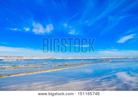 Pacific northwest ocean beach shoreline.  Wispy white clouds and vibrant blue skies reflecting on wet sandy beach.  Scenic travel destination.